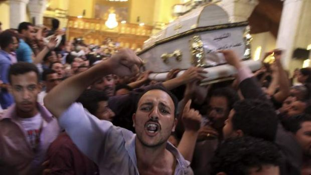 Angry confrontation: Coptic Christians carry the coffins of men who died during clashes between Muslims and Christians ...