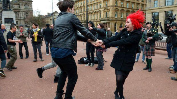 People dance in celebration in Glasgow.