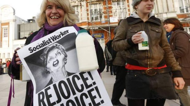 Revellers hold up posters to celebrate the death of Britain's former prime minister Margaret Thatcher.