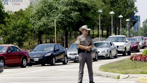 In lockdown: A Texas State Trooper stands at an entrance of the campus.