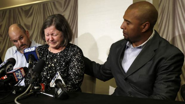 Enduring pain: Former NFL player Dorsey Levens comforts Mary Ann Easterling, the widow of former NFL player Ray ...