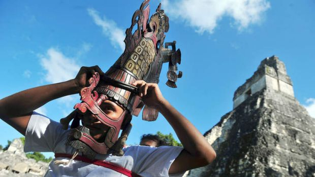 Joining the dots: A man places a Mayan mask on his head in front of a Mayan temple in the city of Tikal.