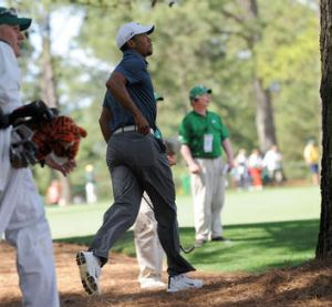 Tiger Woods of the US rushes to look after hitting from a rough on the 9th hole during the third round.