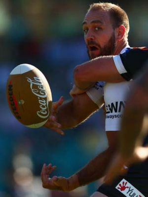 Eye on the ball: Jason Nightingale of the Dragons gets a pass away against the Wests Tigers.