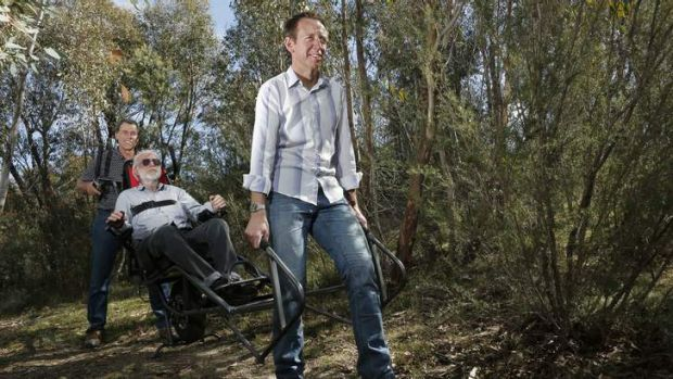 National Parks Association president Rod Griffiths(centre) gets some help testing out a new wheelchair from Peter Clarke ...