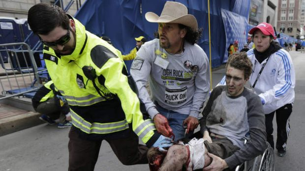 An injured man is helped through the streets of Boston after the bombings.