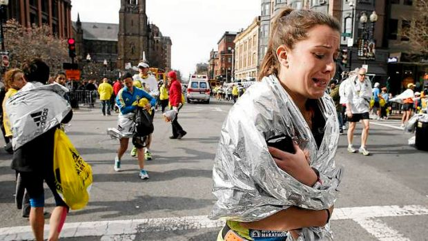 An unidentified Boston Marathon runner leaves the course crying near Copley Square following two bomb blasts.