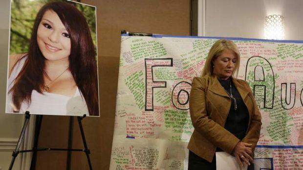 Sheila Pott, mother of Audrie Pott, stands by a photograph of her daughter during a news conference.