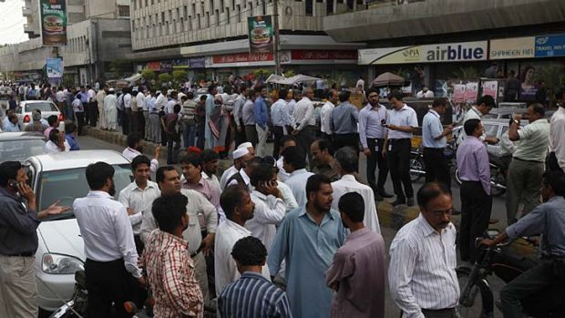 People stand outside their offices after the tremor was felt in Karachi.