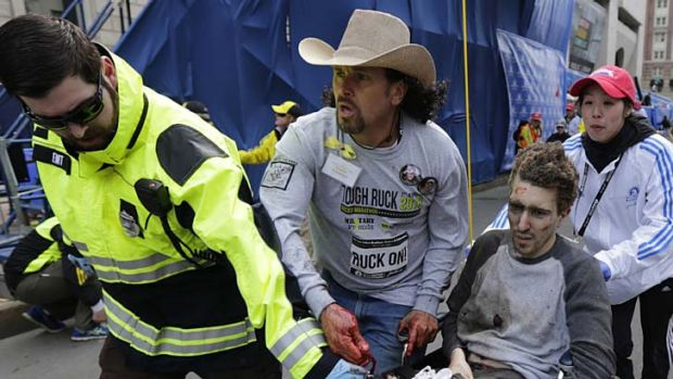 Jeff Bauman is rushed from the scene by Carlos Arredondo and other rescue workers