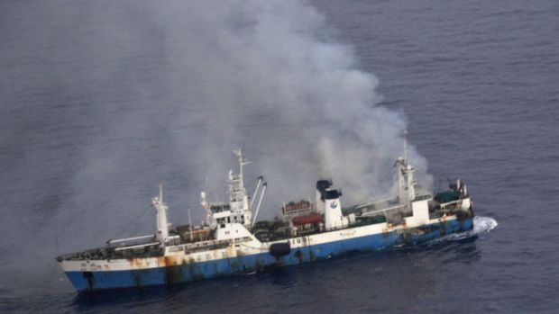 In this picture released by Chile's Air Force, smoke billows from a Chinese factory fishing ship Kai Xin just off the ...