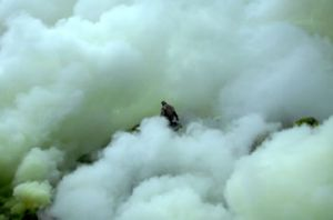 An Indonesian worker gathering sulphur deposits at the crater of Ijen Volcano, in East Java, is enveloped by sulphur steam.