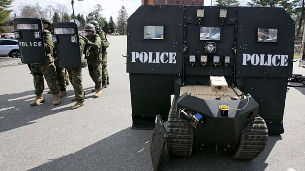 A team of police line up behind a pair of hand-held bulletproof shields, showing the relative lack of protection ...