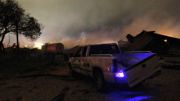 A damaged car sits idle as smoke rises in the background.
