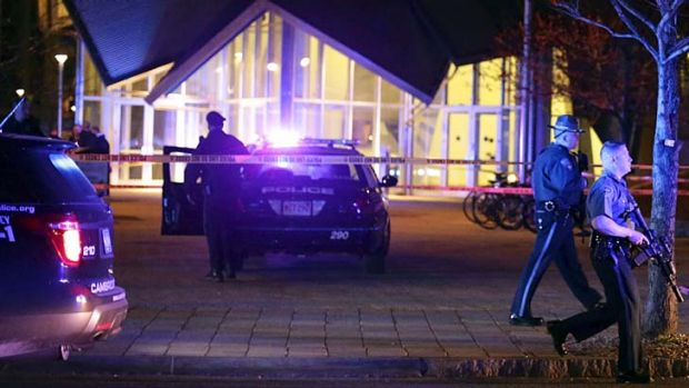 Police officers secure a school building at the MIT after the shooting of a police officer.