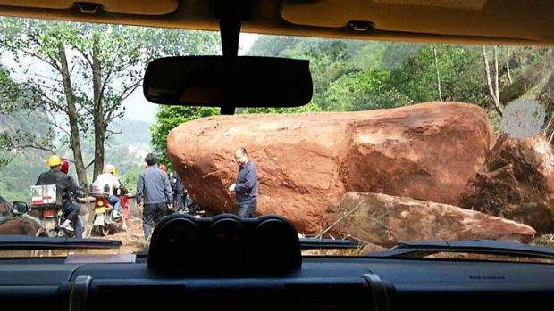 A giant rock blocks the road, about 20 kilometers (12.5 miles)  from the county seat of Lushan in Ya'an city, southwest ...
