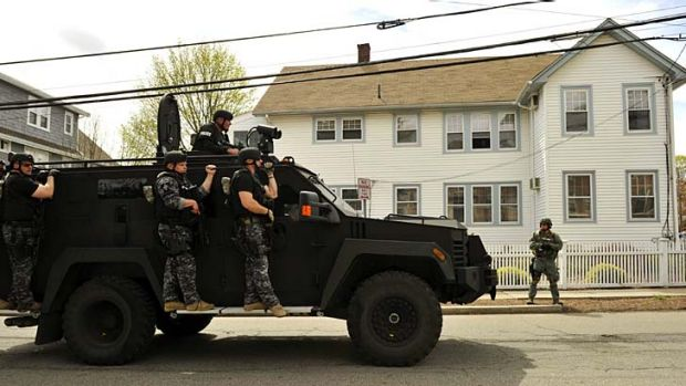 Manhunt: A police SWAT team search houses for the second of two suspects wanted in the Boston Marathon bombings.