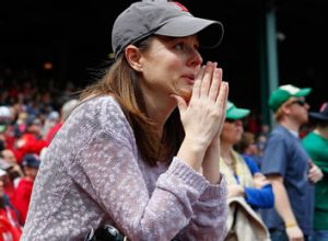 A woman sheds a tear during pre-game ceremonies in honor of the Marathon bombing victims before a game between the ...