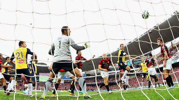 Patrick Zwaanswijk of the Mariners heads the ball past Wanderers goalkeeper Ante Covic to open his team's account in the ...