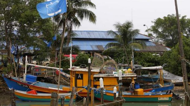 Fishing for votes: A flag of Malaysia's ruling National Front coalition flies as a man works on a fishing boat in ...