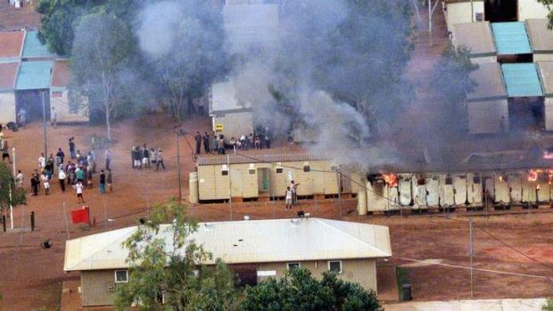 Detainees at Curtin detention centre watch as a building burns during a 2001 riot.