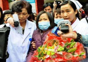 Breathing more easily ... H7N9 bird flu patient, surnamed Jia (C), is escorted from a hospital upon her recovery in ...