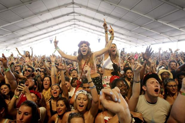 Concert-goers cheer as they watch the performance by 2 Chainz during the Coachella Music Festival in Indio, California.