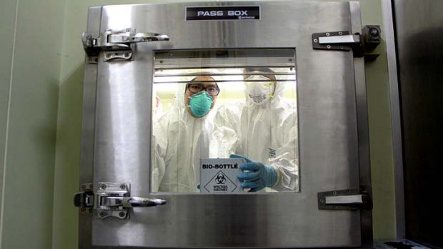 Health personnel hold a container with H7N9 viral specimens from China at the National Influenza Centre in Taiwan.