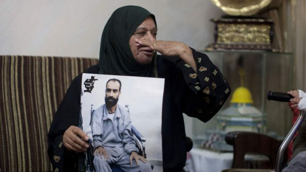 Samer Issawi's mother Layla holds his picture after the deal was announced.