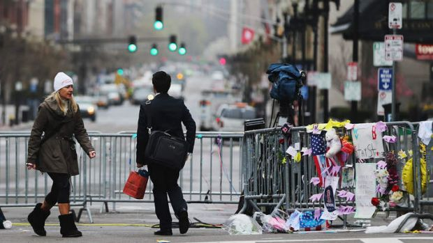 Crime scene: People walk past a barricade and makeshift memorial blocking a still closed section of Boylston Street near ...