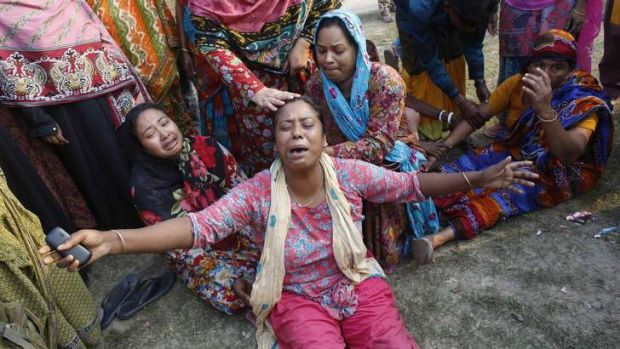 Relatives of victims mourn outside the remains of the collapsed factory building.