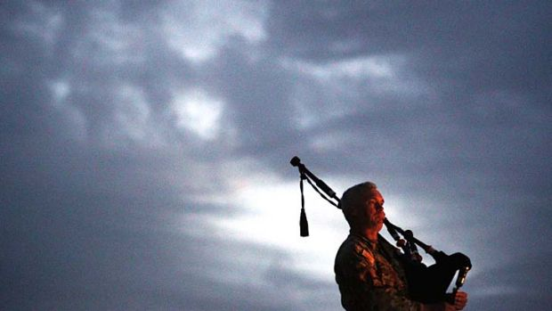 As the sun rises: A bagpiper at Tarin Kowt base's dawn service.