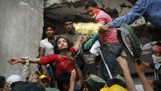 Alive: A survivor is lifted out of the rubble by rescuers on Thursday.