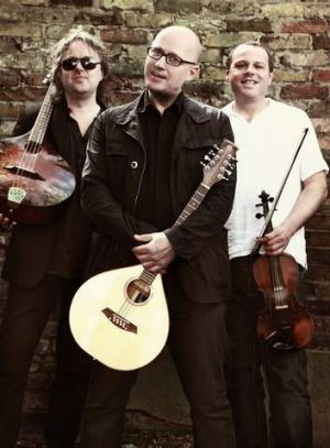 Adrian Edmondson (centre) swapped stand-up comedy for punk songs on folk instruments with Troy Donockley (left) and Andy ...