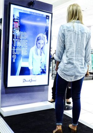 A David Jones customer at a photo booth that snaps a shot of them in jeans to share on social media.