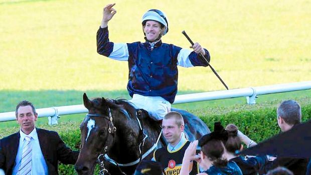 Hugh Bowman greets the crowd as he comes back to scale aboard the Sydney Cup winner, Mourayan.