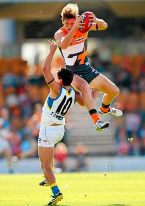 Giant leap: Adam Tomlinson marks over the Suns' Dion Prestia in Gold Coast's victory at Manuka Oval on Saturday.