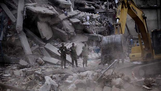Bleak outlook: Bangladeshi soldiers stand in the rubble at the site where a building collapsed near Dhaka.