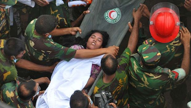 Hard work: Soldiers rescue a woman from the rubble of the the Rana Plaza on Friday, two days after the factory building ...