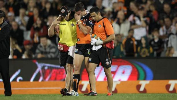 Unlucky break: Tim Moltzen is escorted off the ground after suffering a season-ending knee injury against the Broncos.
