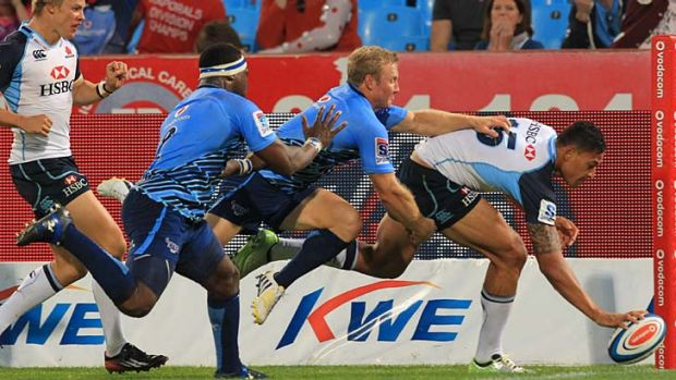 Rare bright moment: Israel Folau of the Waratahs scores a try despite being pursued by Jano Vermaak of the Bulls during ...