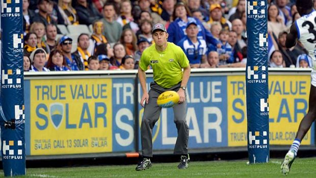 Goal umpire Michael Palm watches the ball bounce at the MCG.