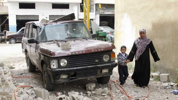 People walk next to a vehicle damaged  by what residents say was a missile fired from the Syrian rebels in Hermel.