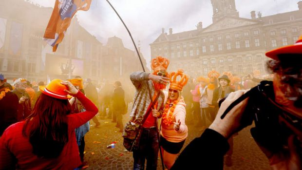 People, some of them wearing orange inflatable plastic crowns, celebrate on the Dam Square on the occasion of the ...