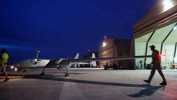 A Heron is towed out of the hangar before take off at Kandahar Airfield .
