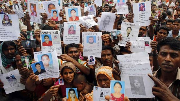 Faces of the fallen: Relatives show pictures of workers believed trapped under the rubble of Rana Plaza.