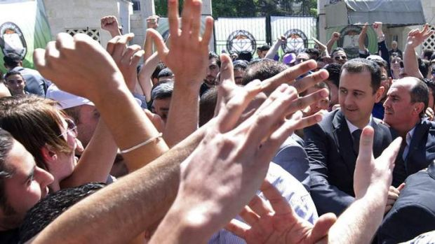 Slaughter: Syria's President Bashar al-Assad greets supporters in Damascus, while his forces were accused of massacres ...