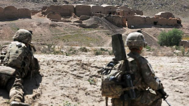 On a mission: US soldiers provide security while their comrades search a village in the Panjwai district of Kandahar ...