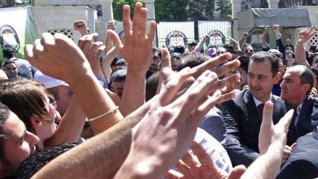 Bid for survival: President Bashar al-Assad among supporters at Damascus University on the weekend.