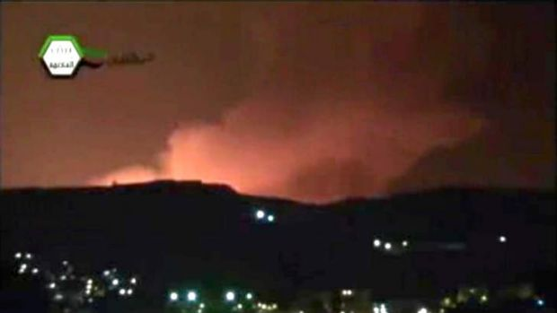 Hit: Smoke and fire fill the skyline over Damascus after an Israeli airstrike.